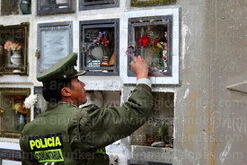 Policeman cleaning tomb in cemetery for Todos Santos festival, La Paz, Bolivia