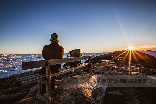 A lone man taking it all in at one of the benches of the blue hiking trail in the Ilulissat Icefjord in Greenland