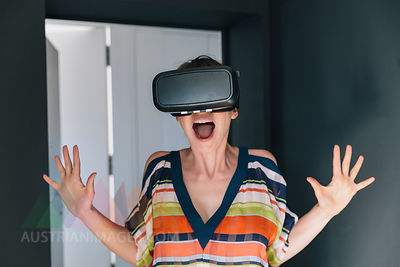 Amazed woman wearing VR glasses making a crazy face