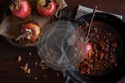 Making toffee apples with ripe red apples. Dipping in toffee.