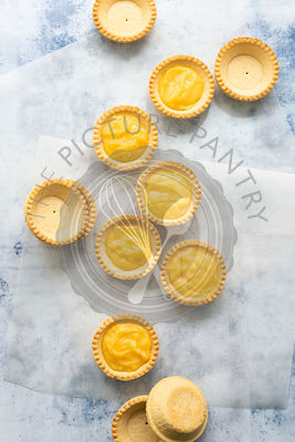 Empty pastry cases and filled lemon tartlets on baking paper.