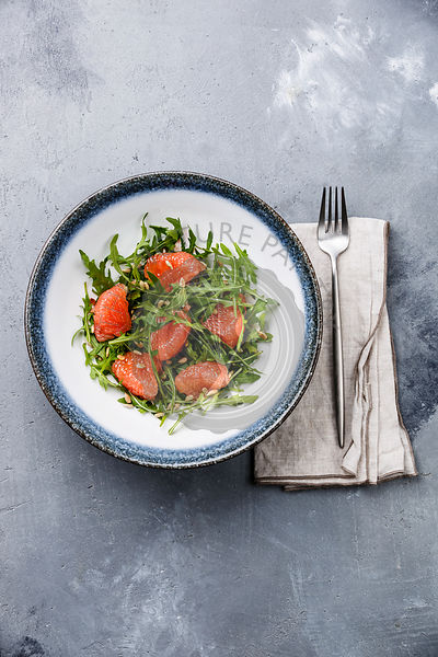 Arugula salad with Grapefruit and sunflower seeds on gray concrete background