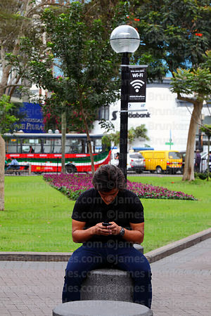 Young man surfing internet on mobile phone in public wifi area in Parque Kennedy, Miraflores, Lima, Peru