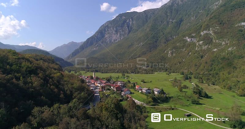 Mountain town, C4K aerial rising drone view of a small alpine town, near soca river, on a sunny summer day, in the Julian alps, Slovenia