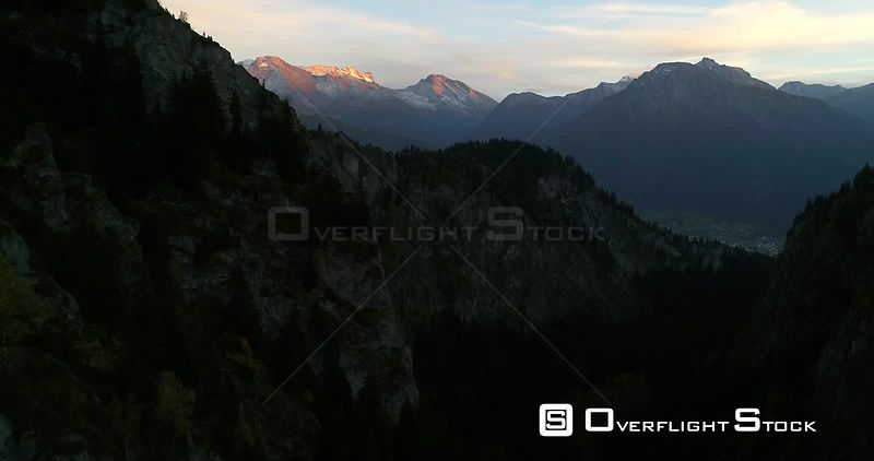 Alpine City, 4k Aerial View Over a Mountain, Revealing a Town, Sunny Autumn Evening Dawn, Brig and Naters, Valais, Alps of Switzerland