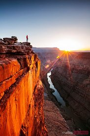 Man standing on the edge of Grand Canyon at sunrise