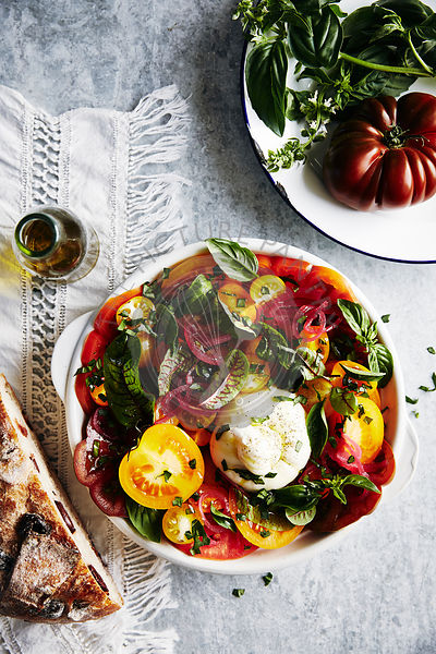 brightly coloured salald of heirloom tomatoes in different colours, lightly picked red onion, herbs, greens, olive oil, burrata cheese. crusty olive bread.