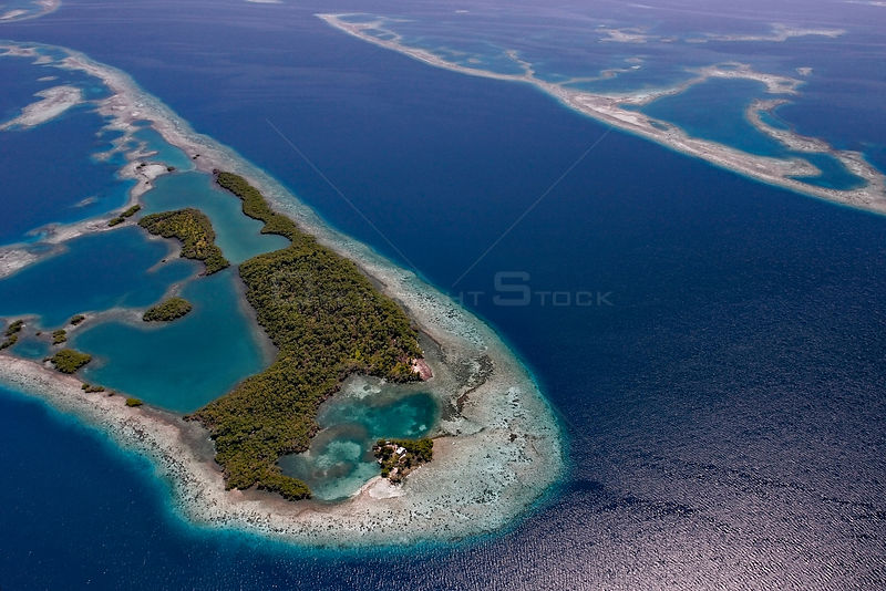 Aerial view of channel through southern Belize barrier reef, with house on small caye. Near Placencia, Belize Barrier Reef Reserve System UNESCO Natural World Heritage Site, Central America.