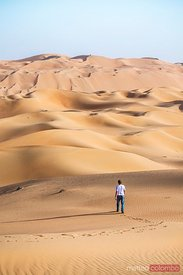 United Arab Emirates, Abu Dhabi. Tourist walking in the desert