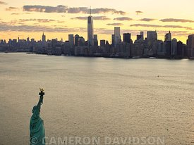 Aerial photograph of Statue of Liberty and Manhattan at sunrise.