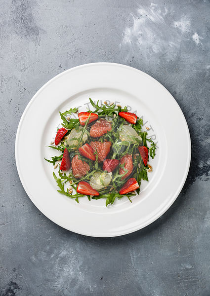 Arugula salad with Grapefruit and Strawberry on gray concrete background