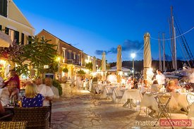 People eating out in the harbour of Fiskardo in a summer evening. Kefalonia, Greek Islands, Greece
