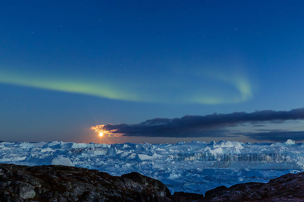 Very early northern lights and full moon above the blue icebergs of the Ilulissat Icefjord in Greenland