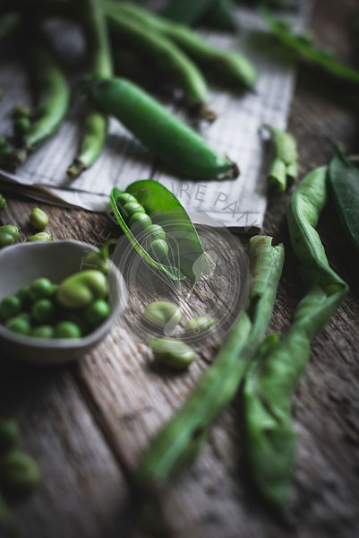 Green peas and green beans on a rustic wooden table