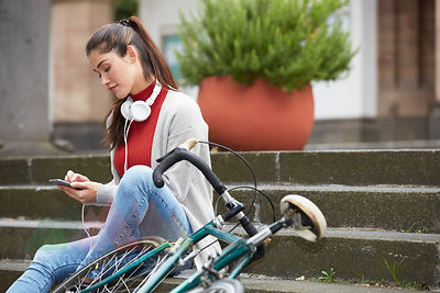 Woman with headphones and bicycle sitting on stairs using cell phone