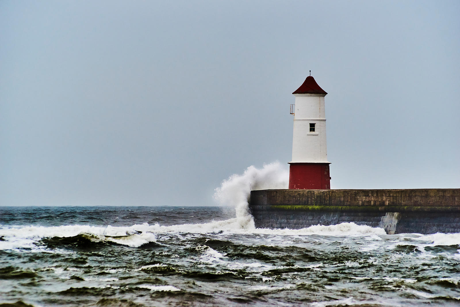 Waves breaking on a lighthouse against a clear blue sky