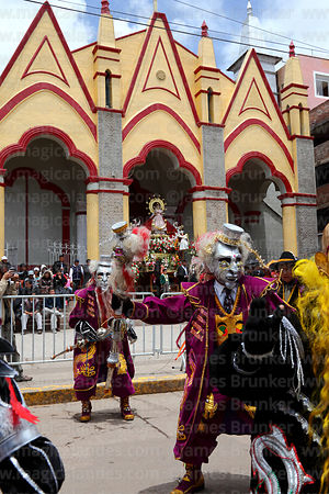 Morenada dancers passing statue of Virgen de la Candelaria in entrance of her Sanctuary, Puno, Peru
