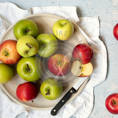 Red and green apples with knife on a round wooden serving board.