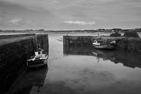 Fishing boats in a harbour at low tide in black and white
