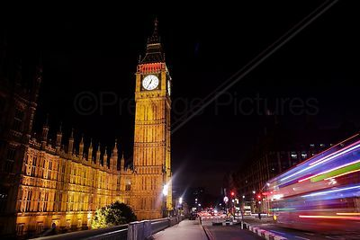 The Big Ben Clock Tower at Night with the Blur of a Red Bus Passing By