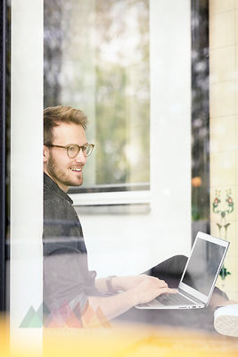 Portrait of smiling man using laptop at the window