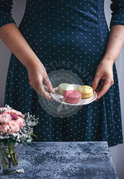 Woman holding a dessert plate with macarons