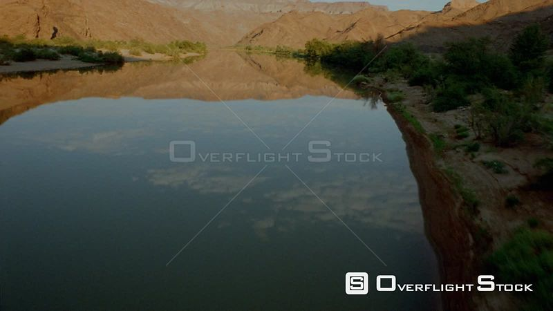 Aerial wide angle shot flying up river with green vegetation on riverbank and mountains and clouds in blue sky reflecting in water Fish River Canyon Namibia