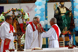 Priest kisses the bible at the start of mass for St Peter and St Paul festival, Arica, Chile
