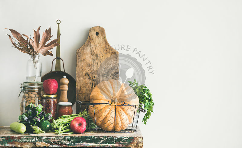 Autumn food ingredients and utensils over wooden cupboard chest