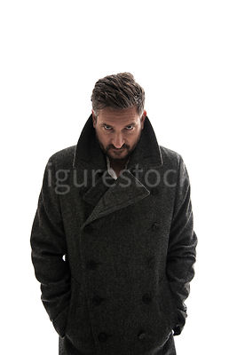 A mystery man in a big coat, looking angrily at camera – shot from eye level.