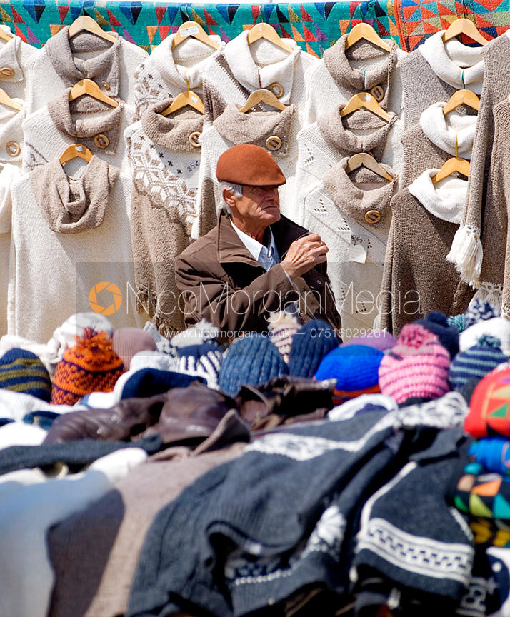 Stall holder at a Portuguese market surrounded by clothes