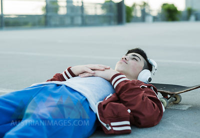 Boy wearing headphones lying on ground outdoors