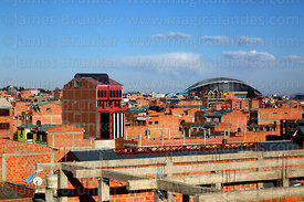 View over brick buildings, Heroes of October sports complex in background, El Alto, Bolivia