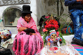 Aymara woman sitting with skull next to mausoleum in cemetery, Ñatitas festival, La Paz, Bolivia