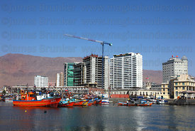 Fishing boats in port , building under construction in background , Iquique , Region I , Chile