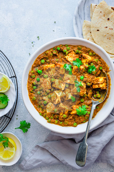 Cottage cheese and pea curry in a ceramic dish. Matar paneer.