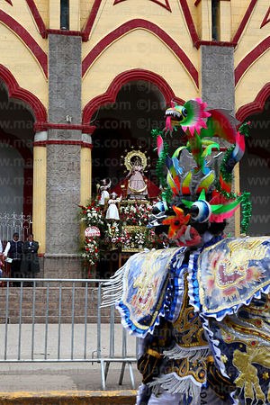 Diablada devil dancer passing statue of Virgen de la Candelaria in entrance of her Sanctuary, Puno, Peru