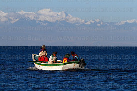 Local family in boat, peaks of Cordillera Real in background, Lake Titicaca, Bolivia