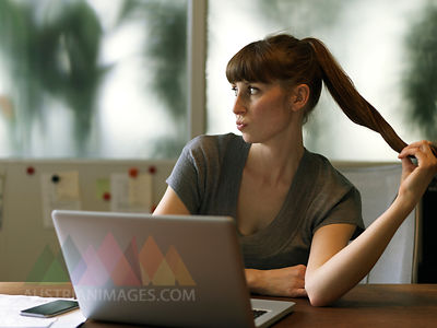 Long-haired woman at desk with laptop