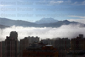 Early morning mist in valley in city centre , Mt Illimani in background , La Paz , Bolivia