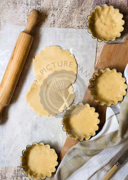 Rolled shortcrust pastry on floured baking paper and in small tart tins.