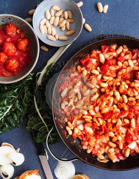 Preparation of Shakshuka with tomatoes, onions and cannellini beans cooking in a pan.