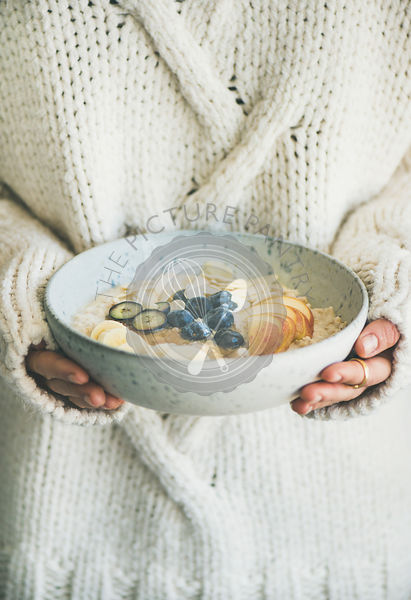 Woman in sweater holding bowl of oatmeal porriage