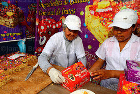 Doña Maria Luisa packing turrón into box for a customer during Señor de los Milagros festival, Lima, Peru