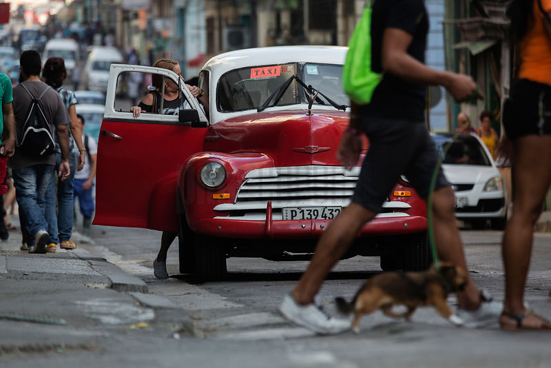 Taxi Picking up a Fare in Busy Havana Street