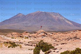 Tourist standing on eroded lava rock formations in front of Cerro Chascos volcano , North Lipez region , Bolivia