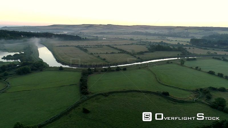 Drone flies slowly over a misty predawn English landscape in West Sussex near the River Arun