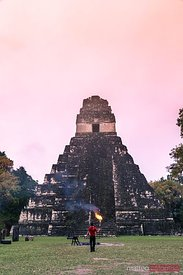 Local man holding a torch in front of mayan temple, Tikal, Guatemala