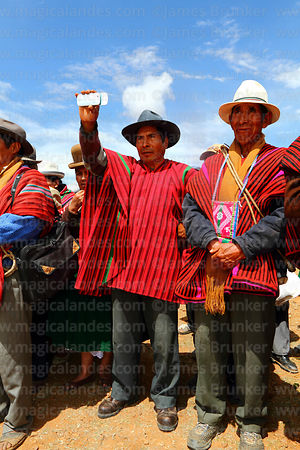 Local community leader using smartphone to film dances at a festival, Umala, Bolivia