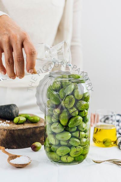 Woman pouring water on green olives in a glass jar. A cup of olive oil and a wooden mallet accompany.